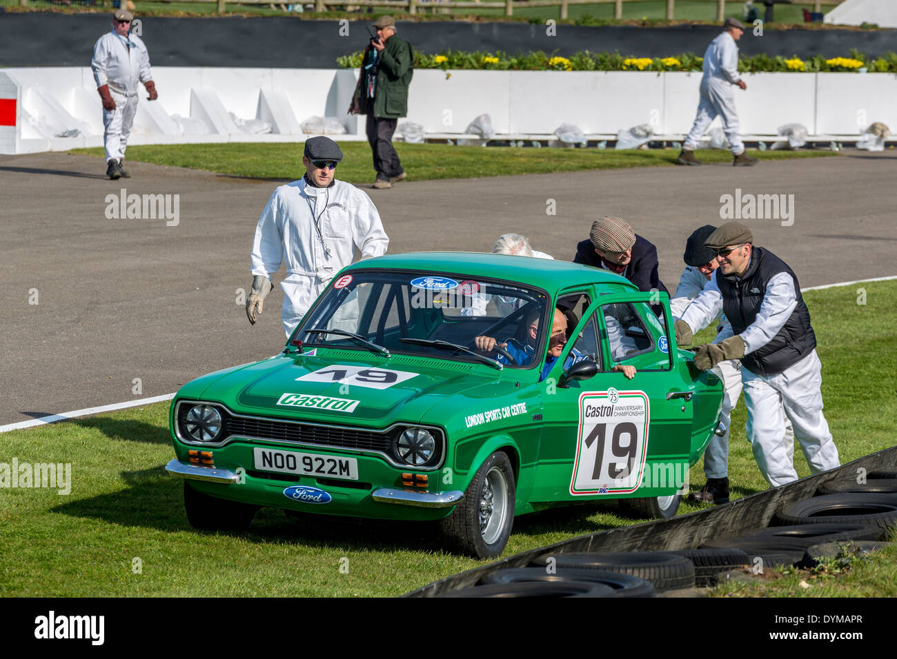 1974 Ford Escort MkI attended by marshals. Driver Peter Clements, Gerry Marshall Trophy Race. 72nd Goodwood Members meeting, UK. - Stock Image