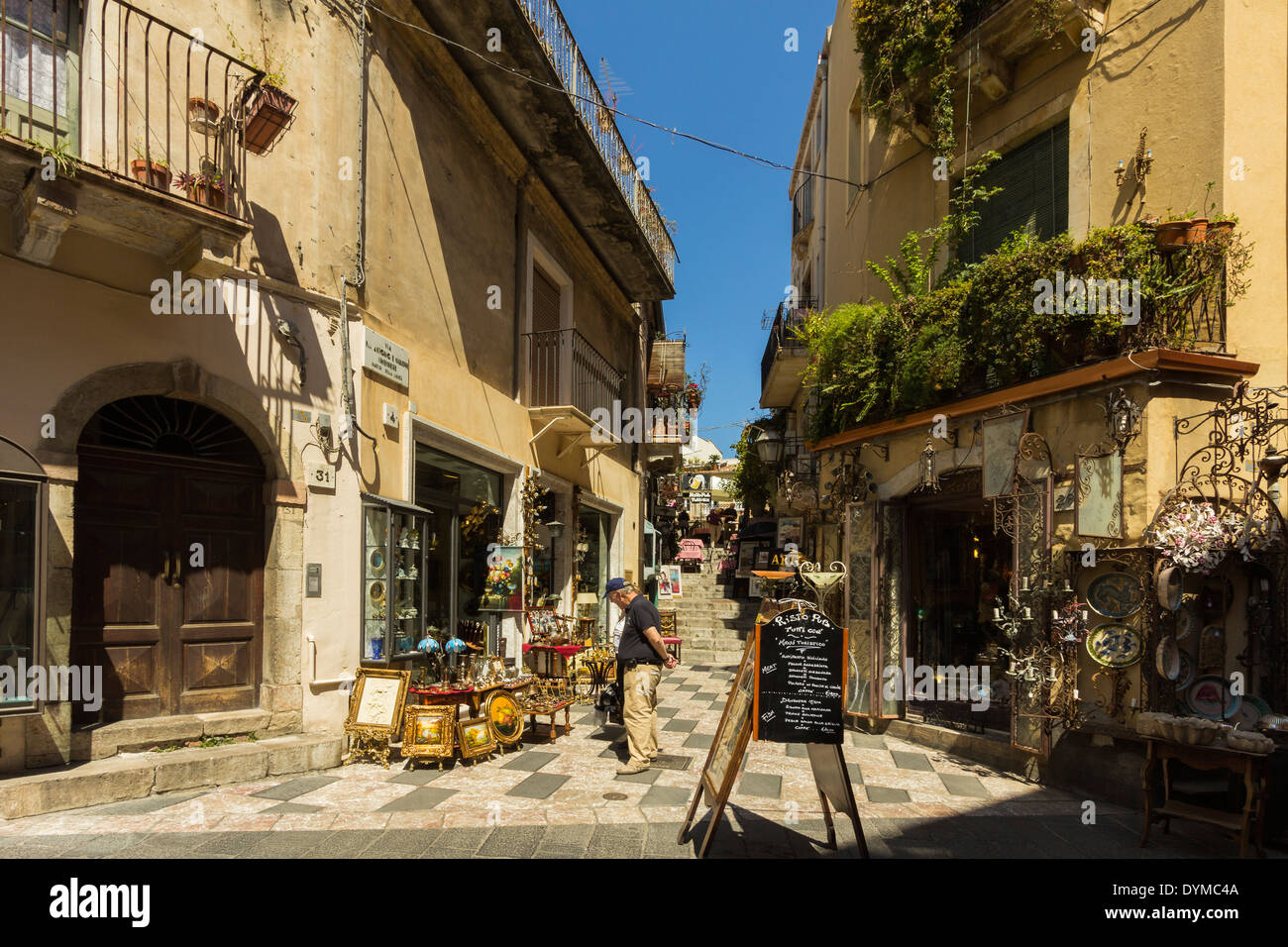 Shops & pub on side street off touristy Corso Umberto in this popular NE tourist town; Taormina, Catania Province, Sicily, Italy - Stock Image
