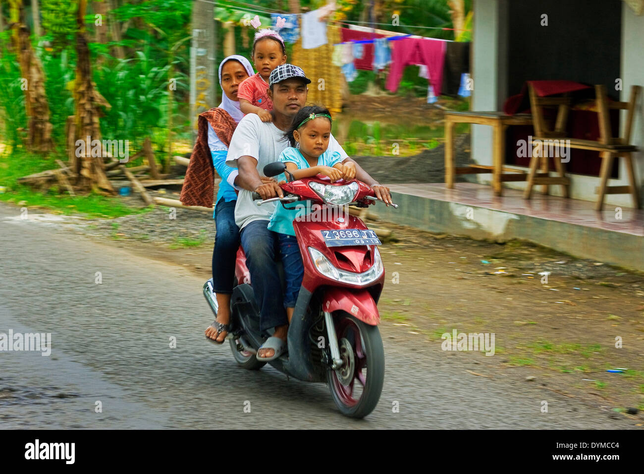 Family without helmets on motorbike in rural district near Pangandaran; Cijulang, West Java, Java, Indonesia - Stock Image