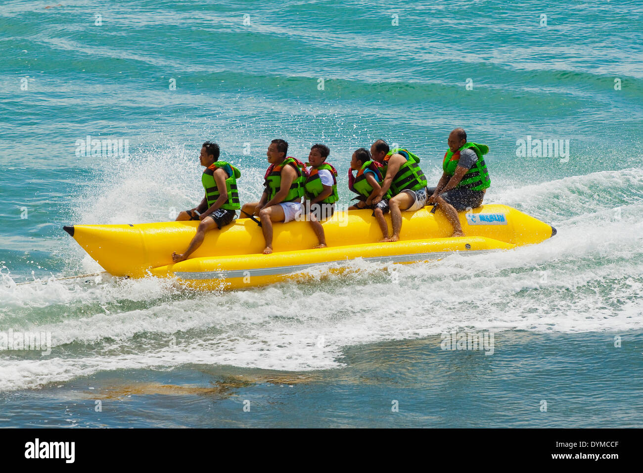 Tourists on inflatable 'banana' at this popular surf break & small resort; Batu Karas, Pangandaran, West Java, Java, Indonesia - Stock Image