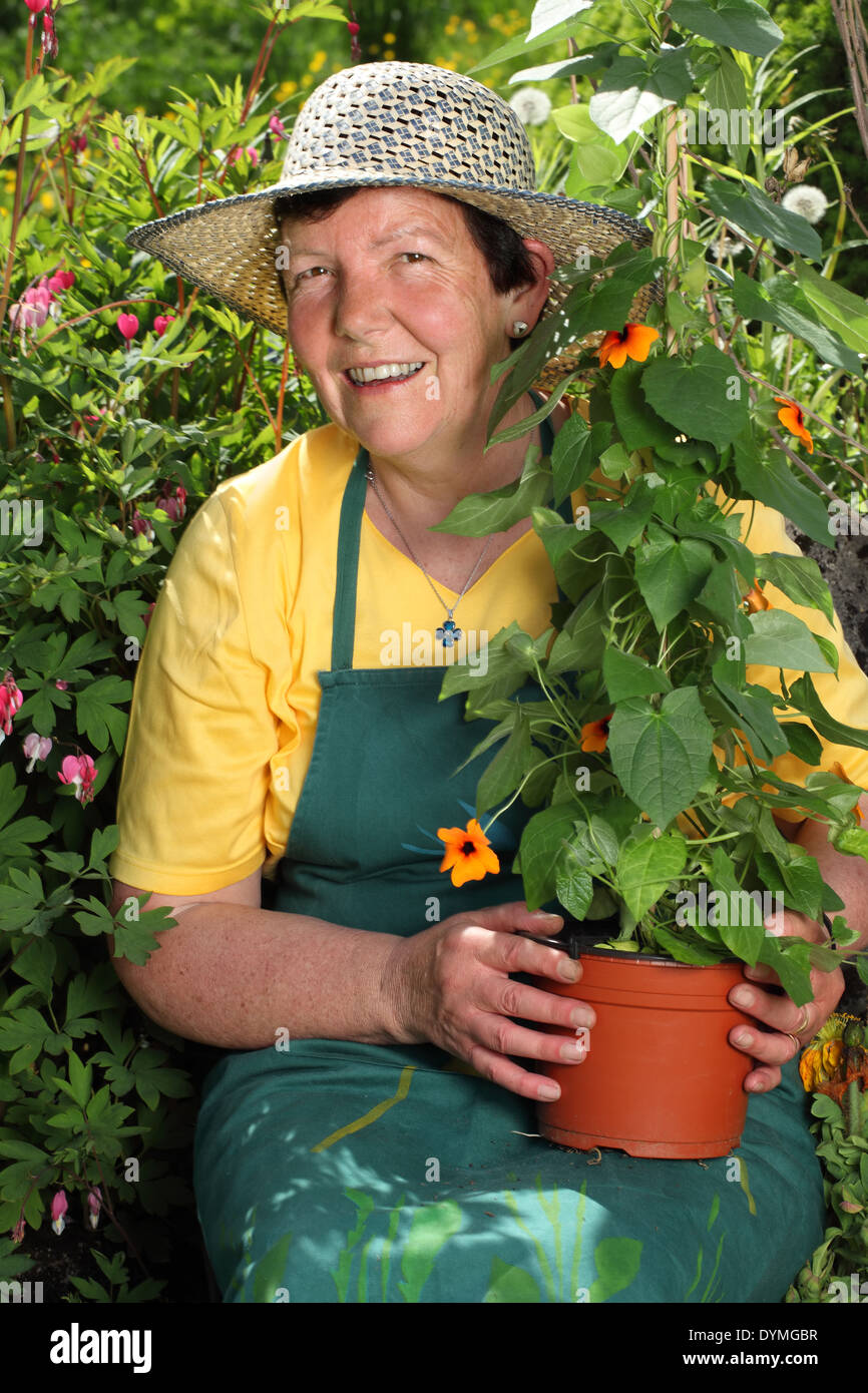 20b8775a Photo of a retired woman holding a potted plant she is about to put into her