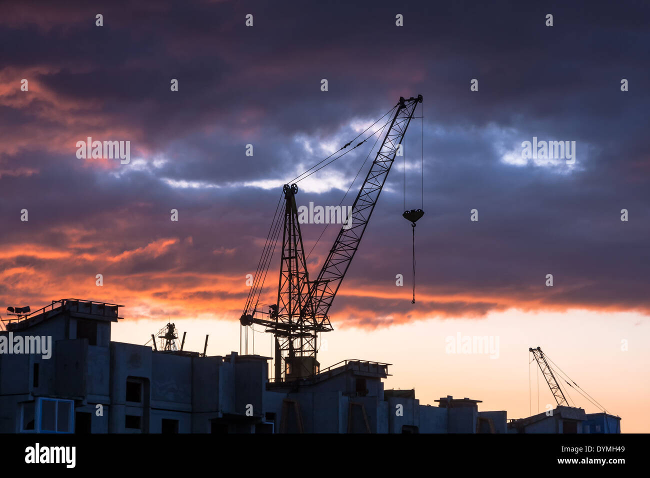 Silhouette of construction crane on dramatic sky background at the sundown - Stock Image