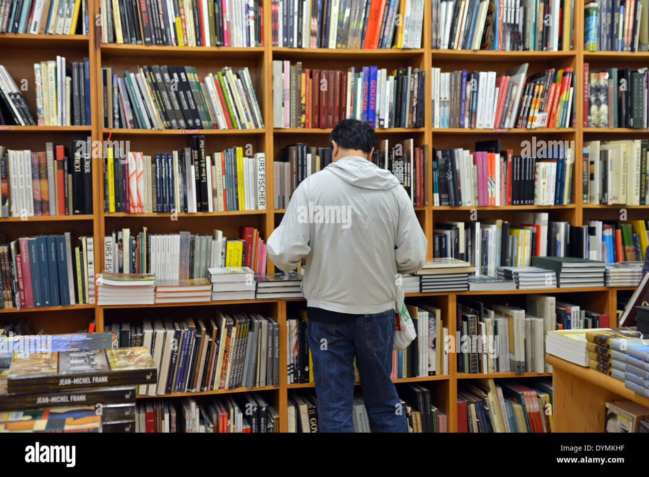 A man in a sweatshirt shopping for books at the Strand Bookstore on Broadway in Greenwich Village, Manhattan, NYC. - Stock Image