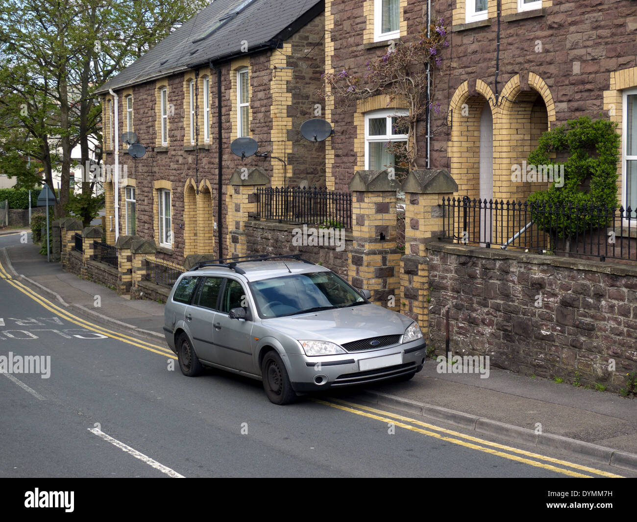 Car parked on pavement and double yellow lines, UK - Stock Image