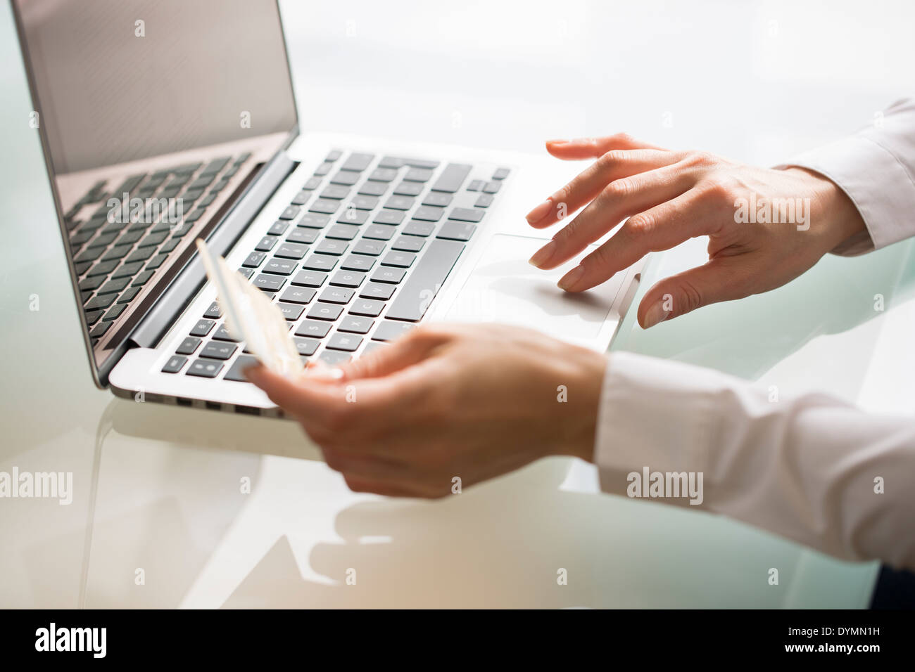 Woman shopping on internet using laptop and credit card - Stock Image