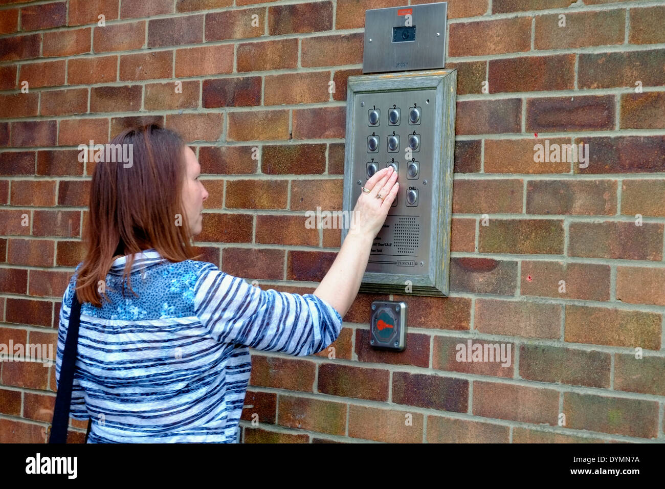 A Middle Aged Woman Using A Tunstall Secure Door Entry Control