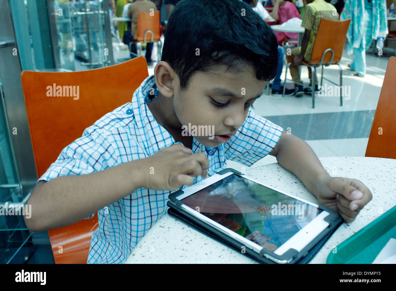 Indian boy playing on an ipad - Stock Image