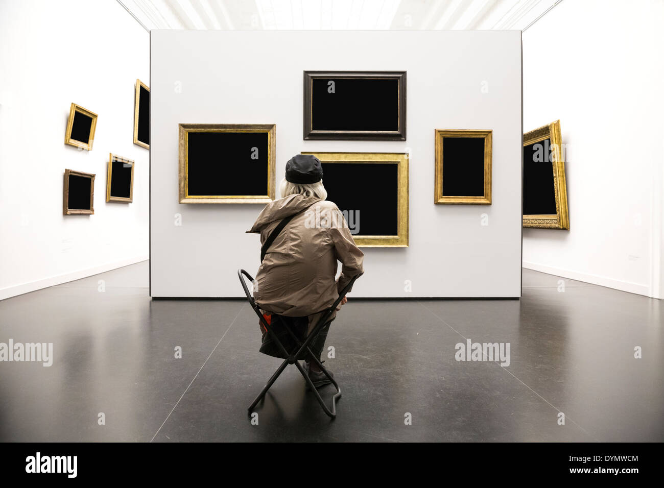 An old lady sitting and starting at blank paintings in an art gallery. Rear view. Long shot. - Stock Image