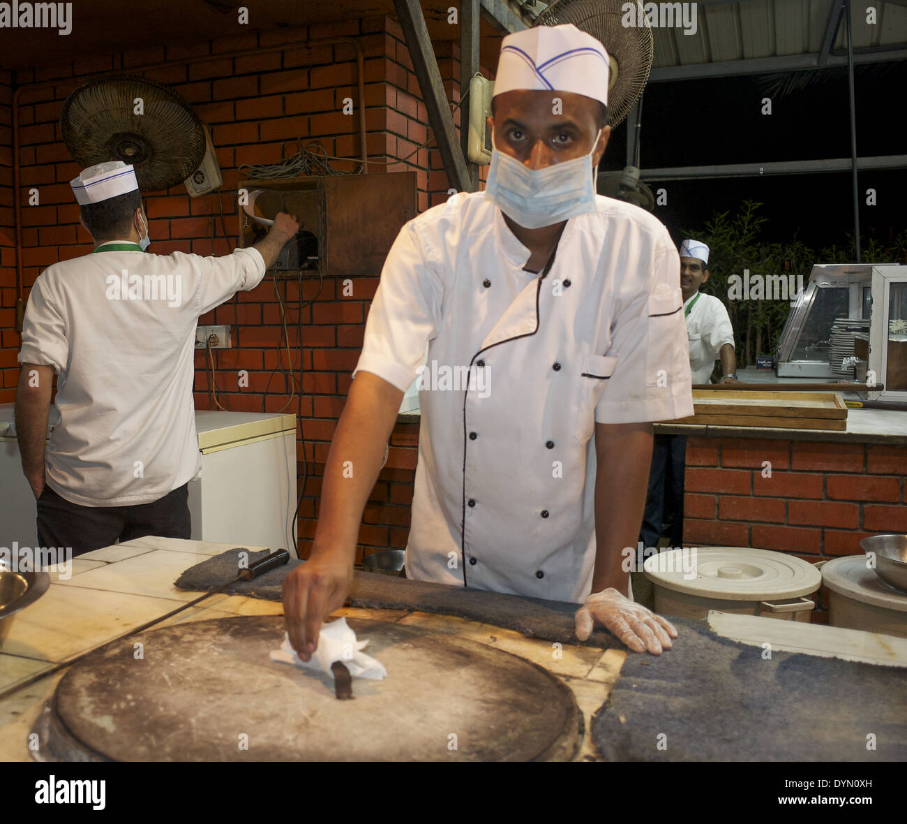Restaurant worker in Jeddah, Saudi Arabia wears a mask to prevent the Middle East Syndrome - Stock Image