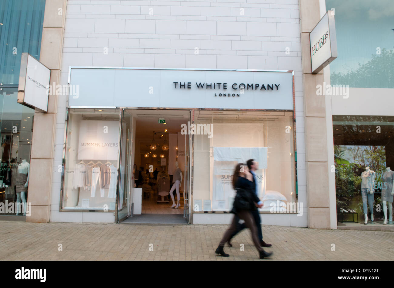 Shoppers walk past the shopfront of the lifestyle store The White Company in up-market Cabot Circus shopping area in Bristol - Stock Image