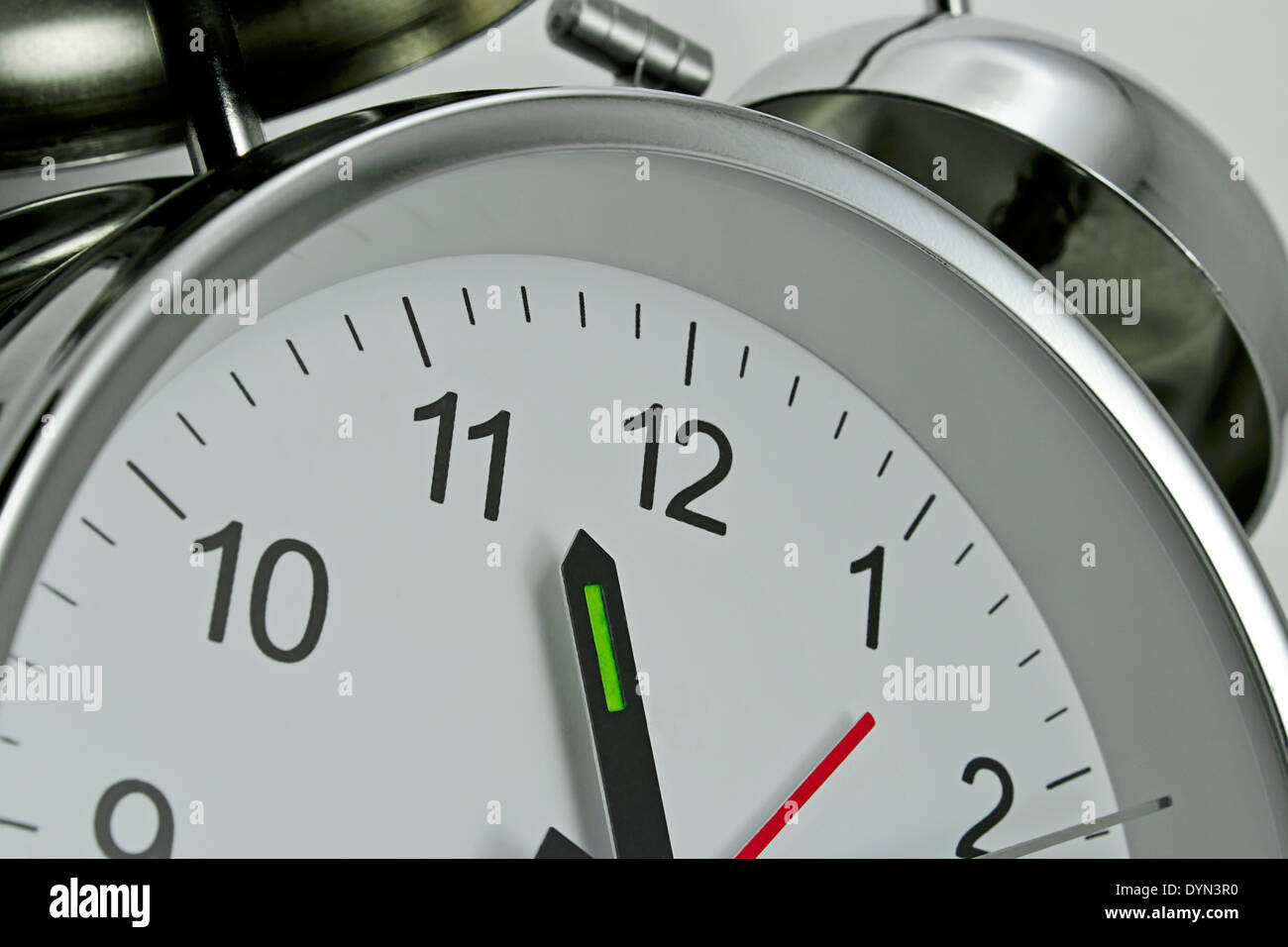 Close up of a Clockface on a traditional chrome silver Alarm clock with bells on the top Stock Photo