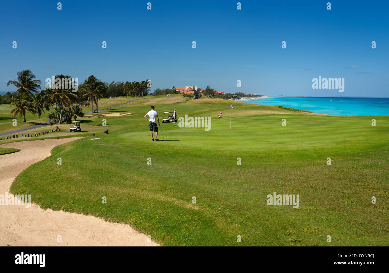 Golfers playing the green of the 18th Hole of the Varadero Golf Club Cuba with Caribbean Ocean - Stock Image