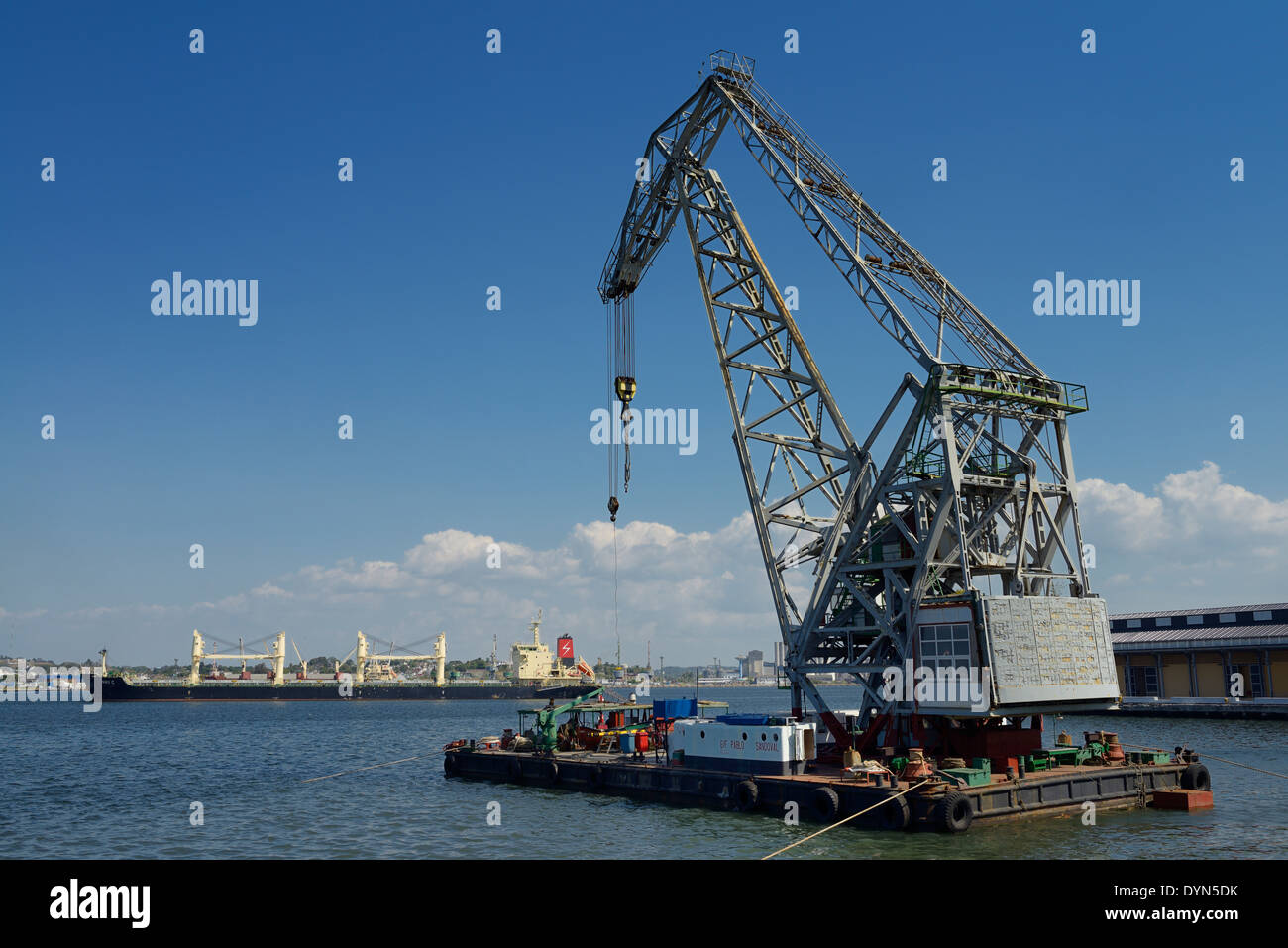 Crane barge and freighter in Havana Bay Harbor Cuba with blue sky - Stock Image