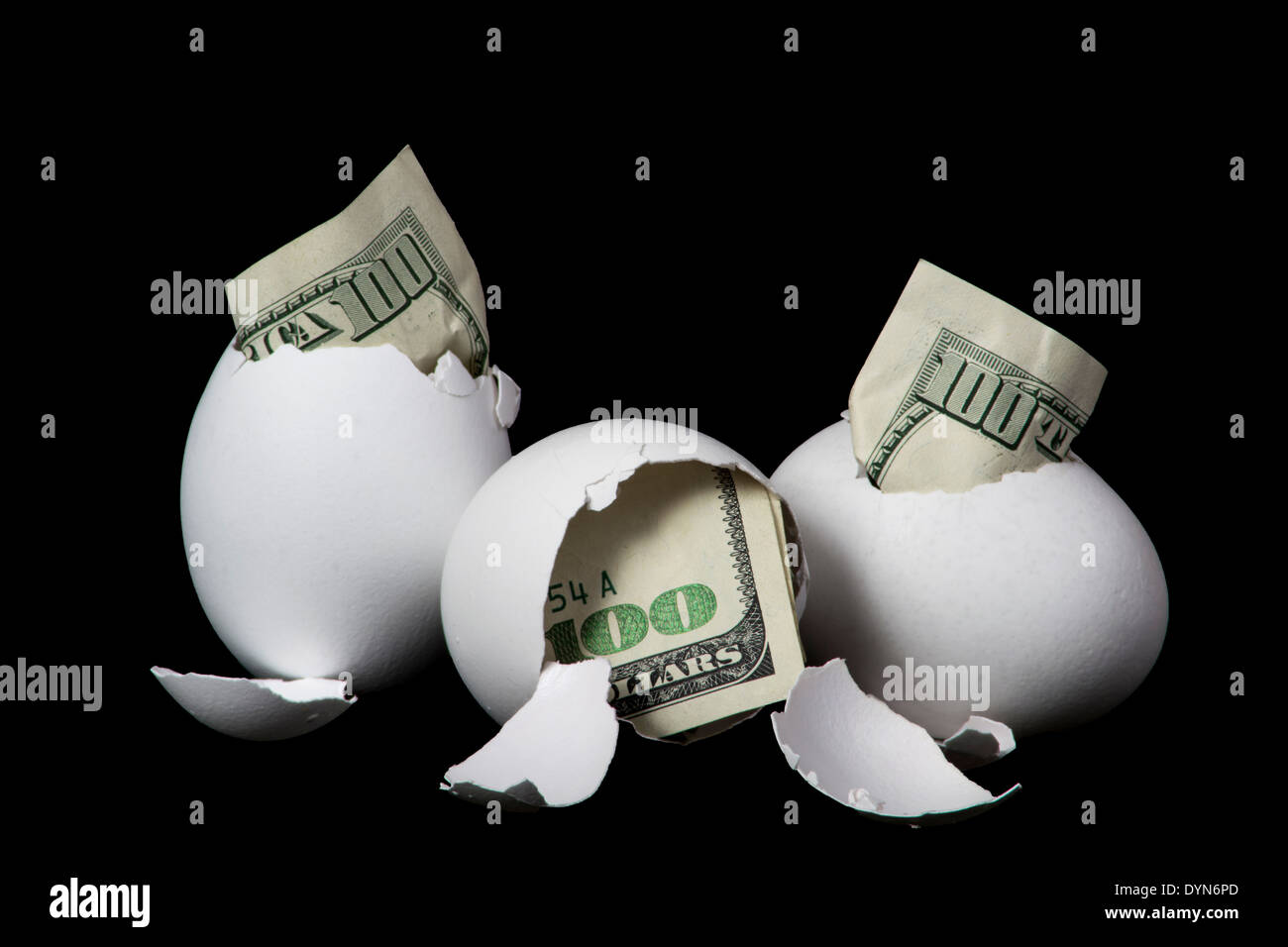 Hundred dollar bills hatching from eggs. - Stock Image
