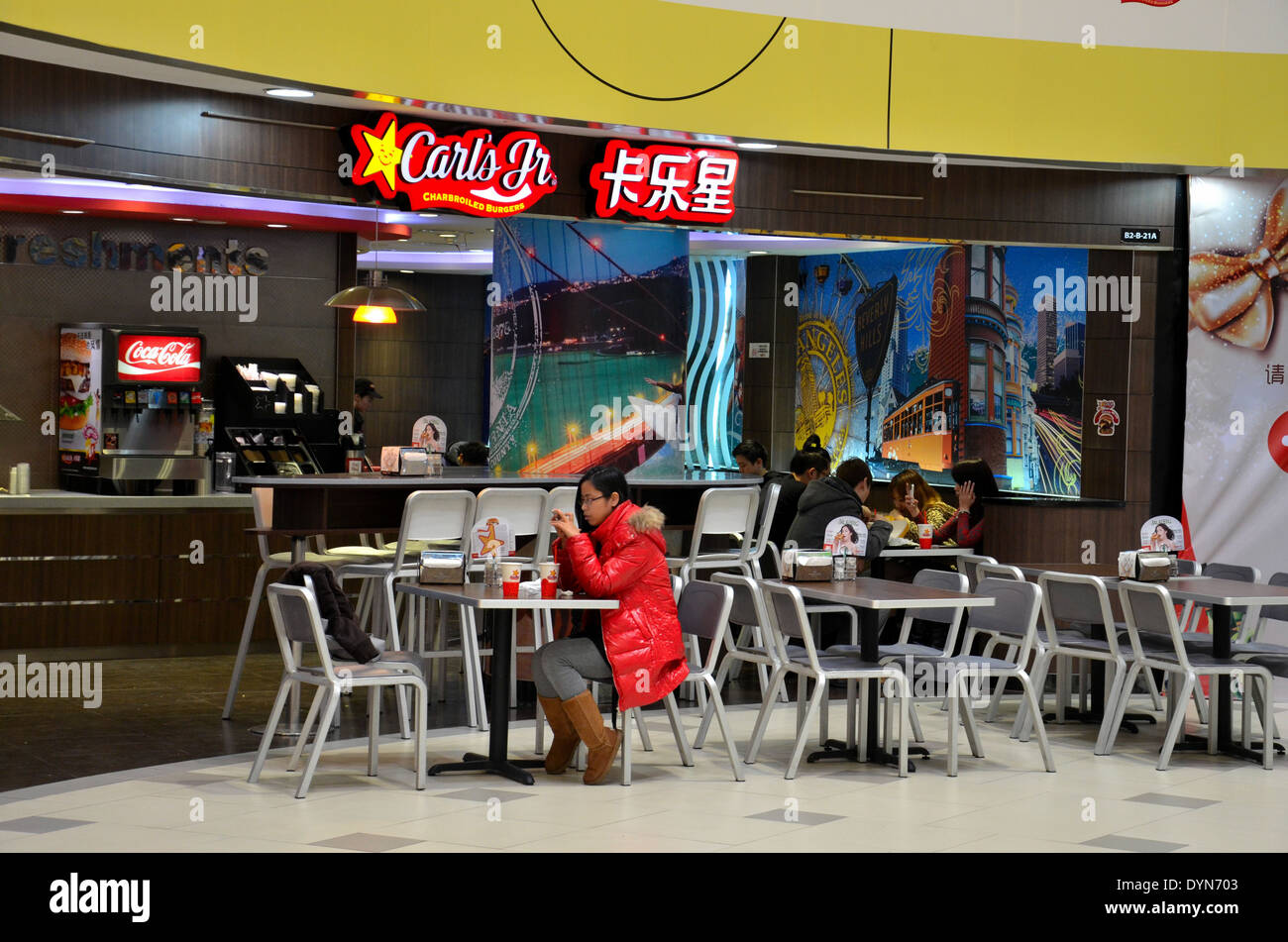 Chinese Girl eats at fast food Carl's Jr restaurant in Shanghai mall China - Stock Image