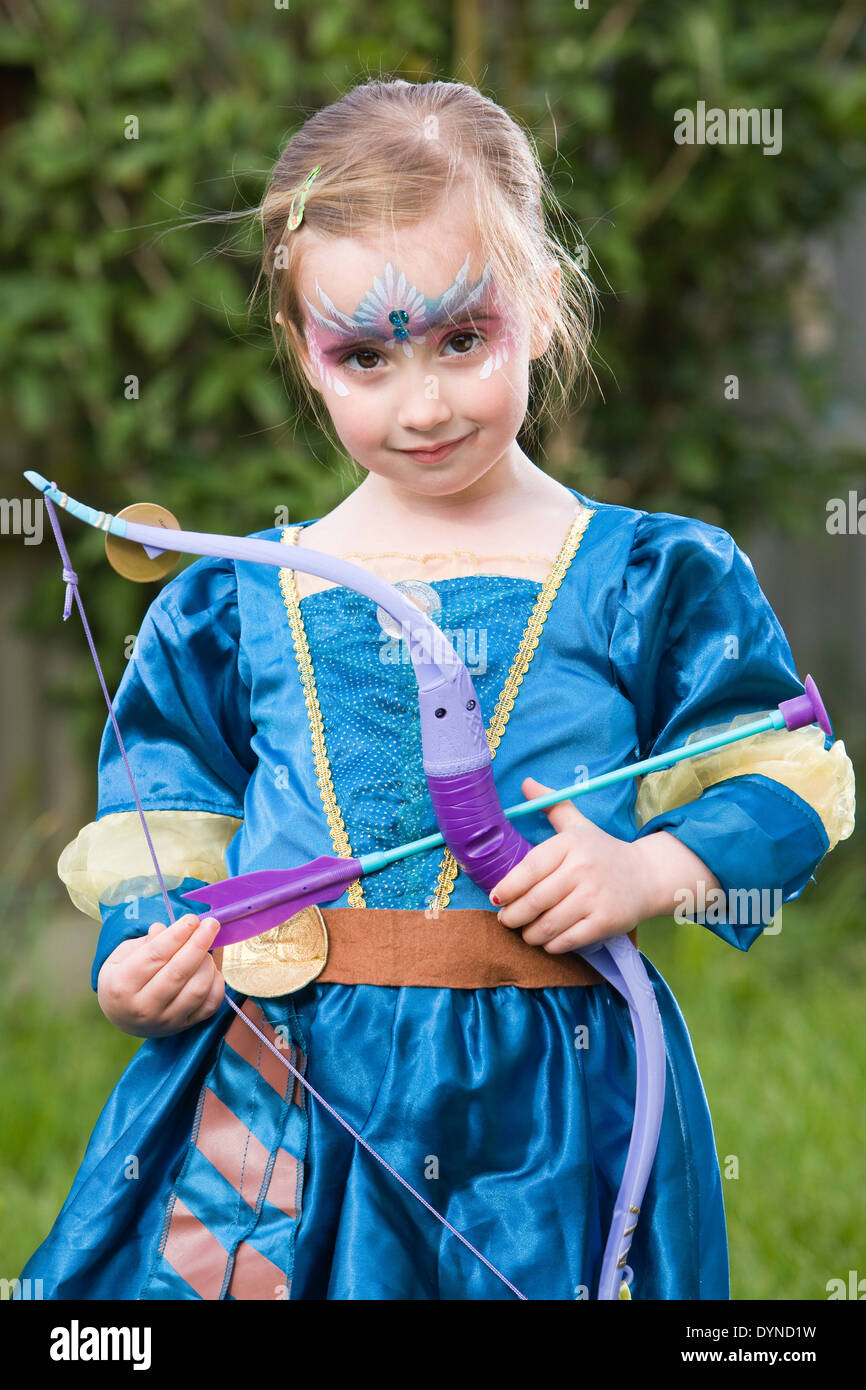 A young girl standing outside wearing a fancy dress princess outfit ...