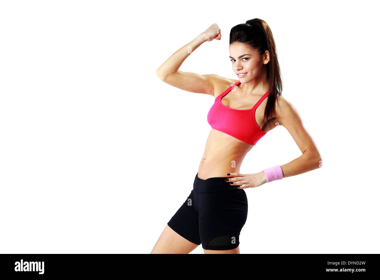 Young happy sport woman showing her biceps over white background - Stock Image