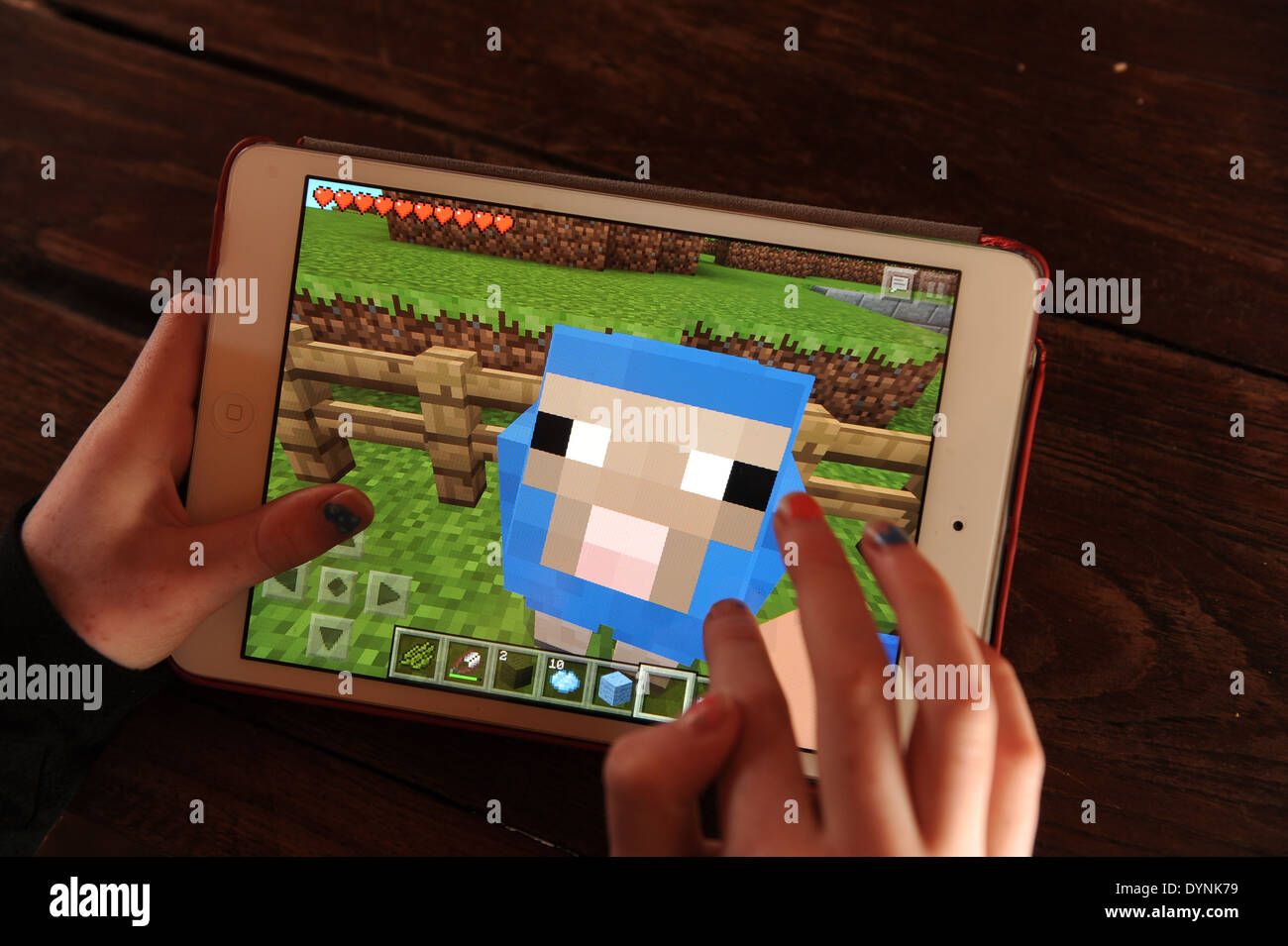 Young girl playing Minecraft on an apple ipad. - Stock Image