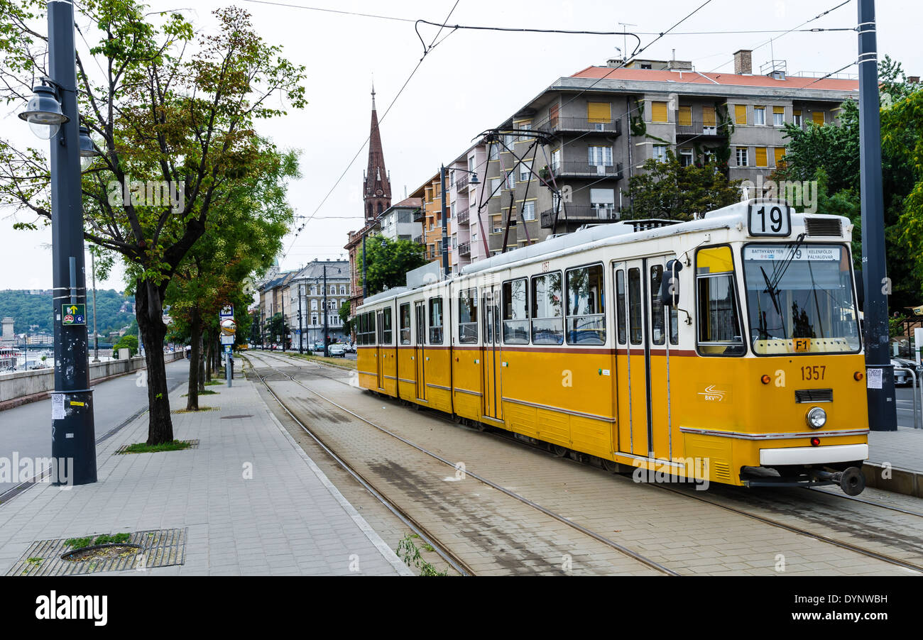 Image Yellow tram on river bank of Danube. Yellow tram is part of transportation system in Budapest, Hungary - Stock Image