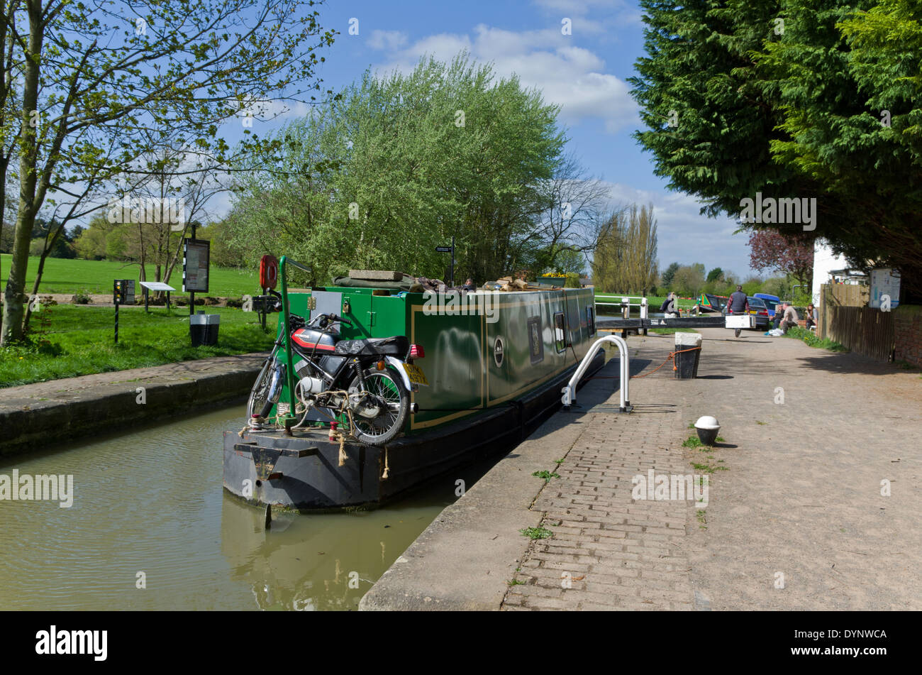 Bicycle strapped to the back of a moored narrowboat, Cosgrove, UK - Stock Image