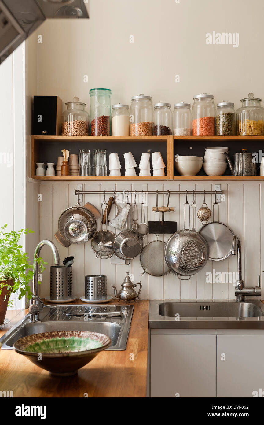 Dried Ingredients On Open Shelving And Utensils Hanging From A Pan Rack In  Kitchen Corner With Sinks And Solid Oak Work Surfaces