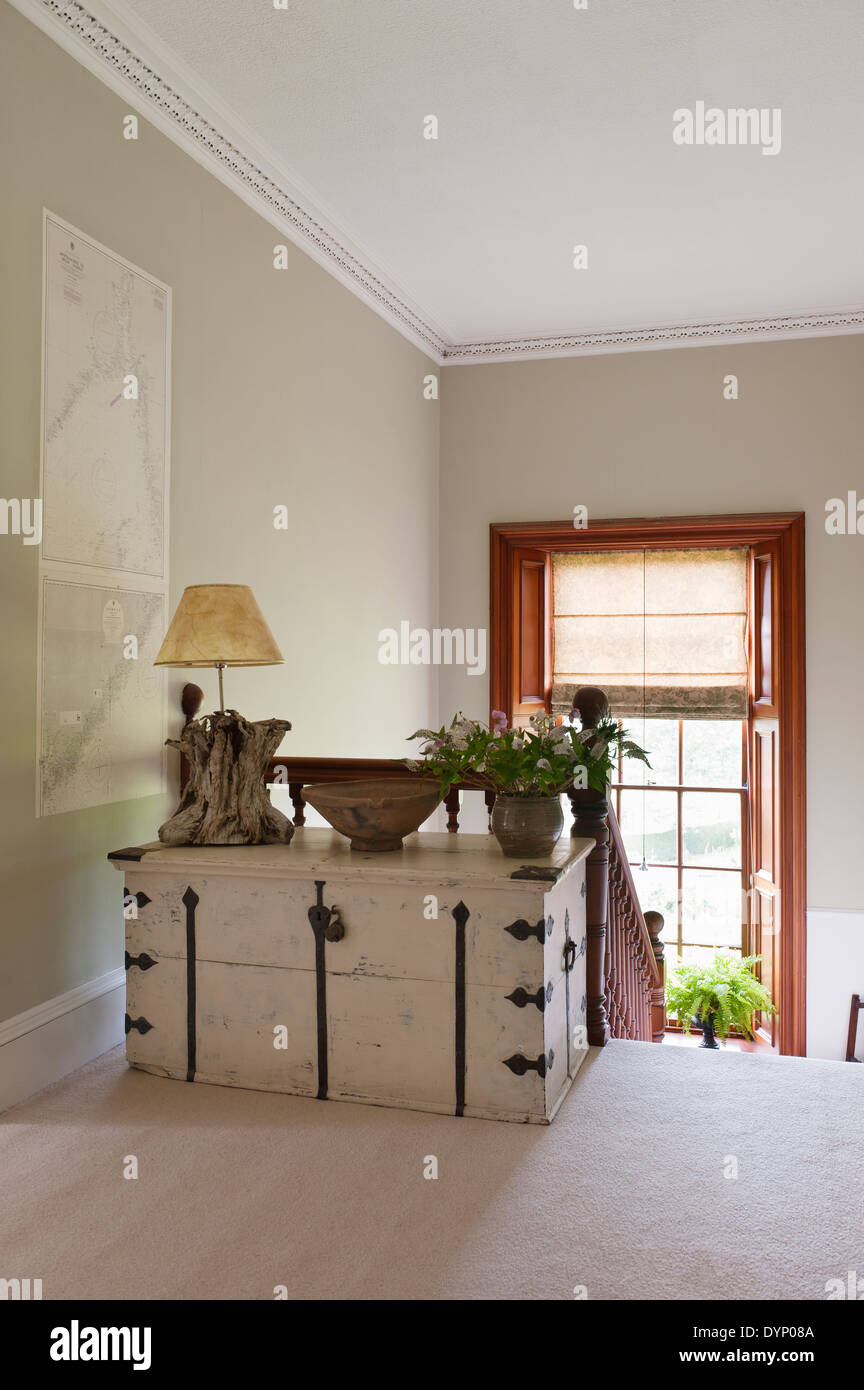 White distressed wooden trunk on upstairs landing - Stock Image