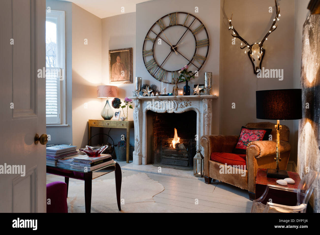 A Graham and Green 'Steeple Wall Clock' above an ornate carved marble fireplace in a living room with a vintage leather armchair - Stock Image
