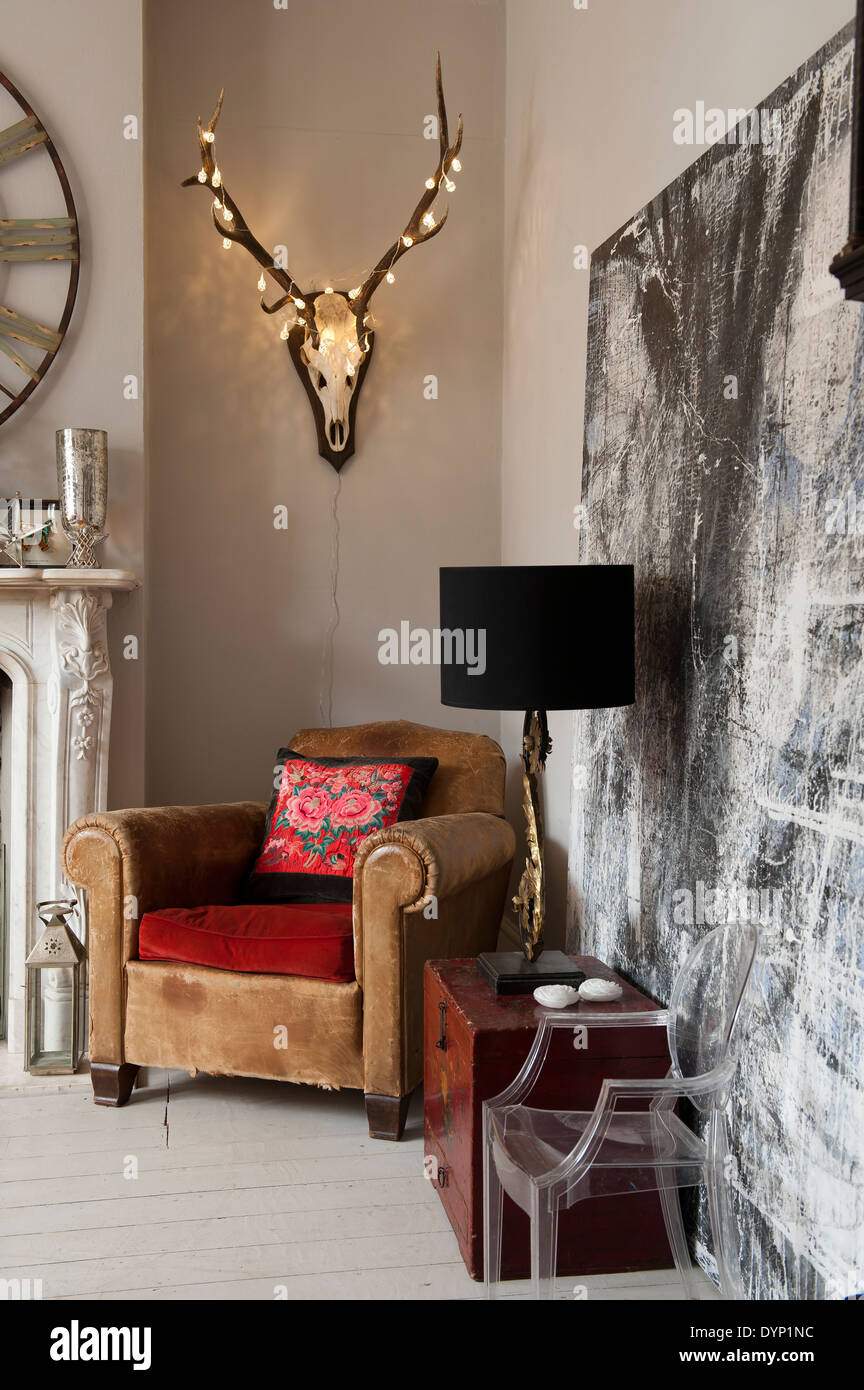 Fairy lights adorn a mounted stag head with antlers on wall above fairy lights adorn a mounted stag head with antlers on wall above vintage leather armchair mozeypictures Gallery
