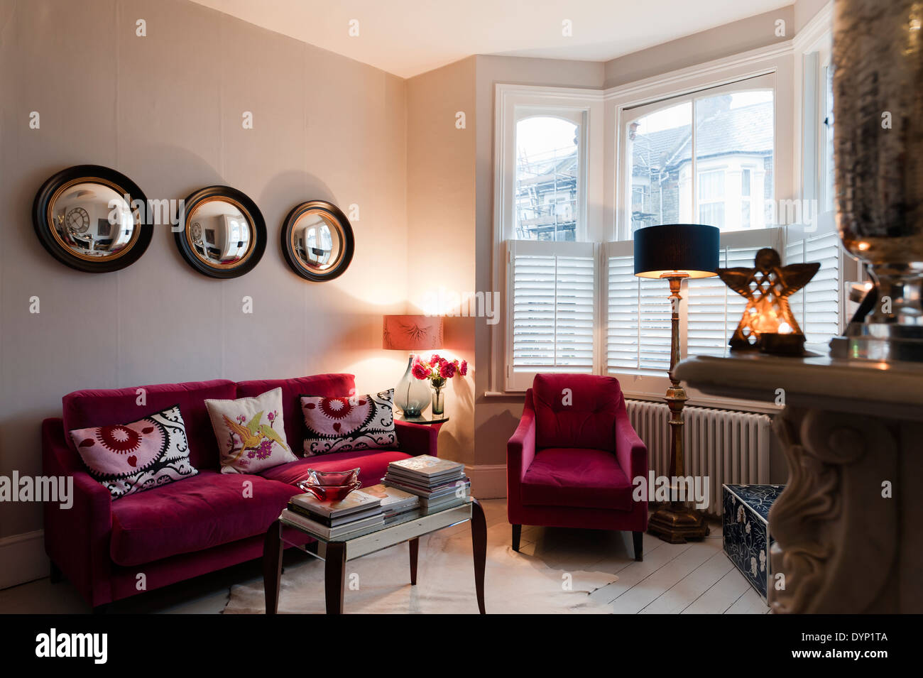 Raspberry Coloured Velvet Furniture In Living Room With Graham And Green  Porthole Wall Mirrors   Stock