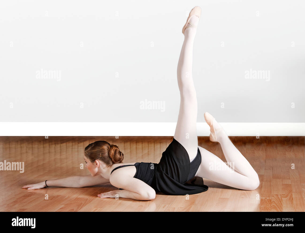 Young female ballet dancer working out on a studio floor - Stock Image