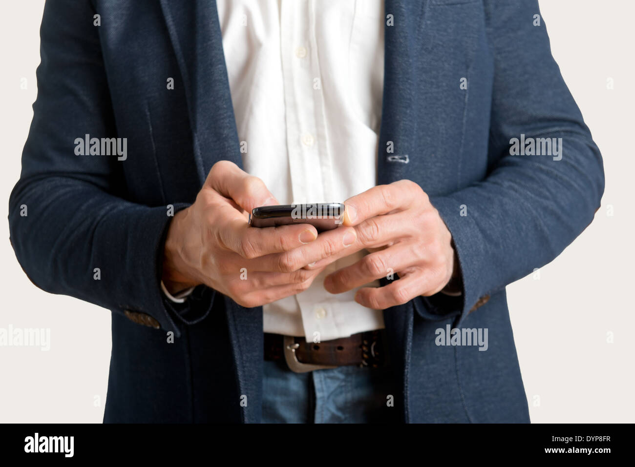 Casual businessman sending a text message on a mobile phone - Stock Image