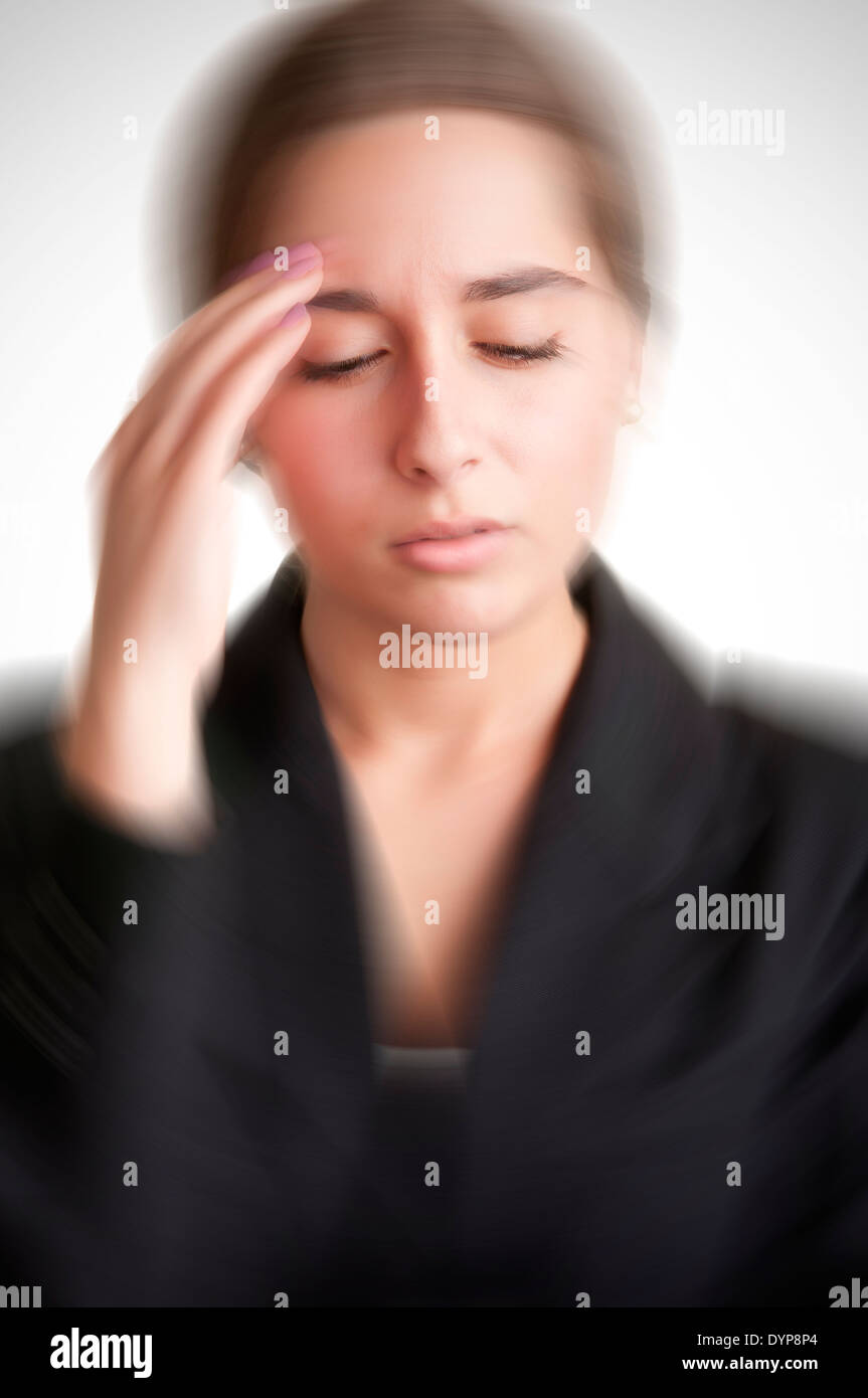 Business woman suffering from an headache, holding her hand to the head, with radial blur effect applied - Stock Image