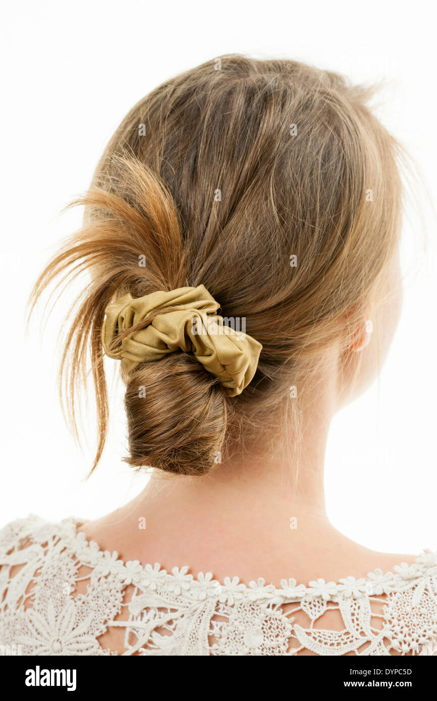 Studio shot of young woman with casual messy chignon hairstyle - Stock Image