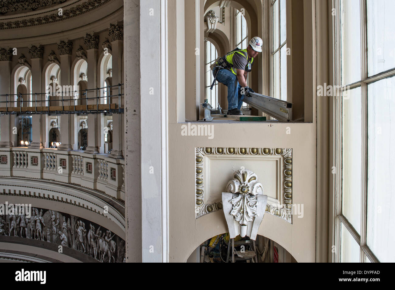 Workers create a scaffold to support a protective canopy inside the Rotunda during the restoration of the US Capitol Dome April 23, 2014 in Washington, DC. The $60 million dollar project is to stop the deterioration of the cast iron dome and preserve it for the future. - Stock Image