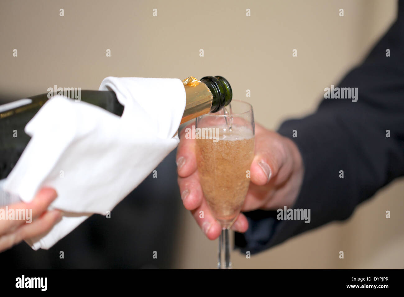 Veuve Durand champagne being poured into a champagne flute by a sommelier at a wedding - Stock Image