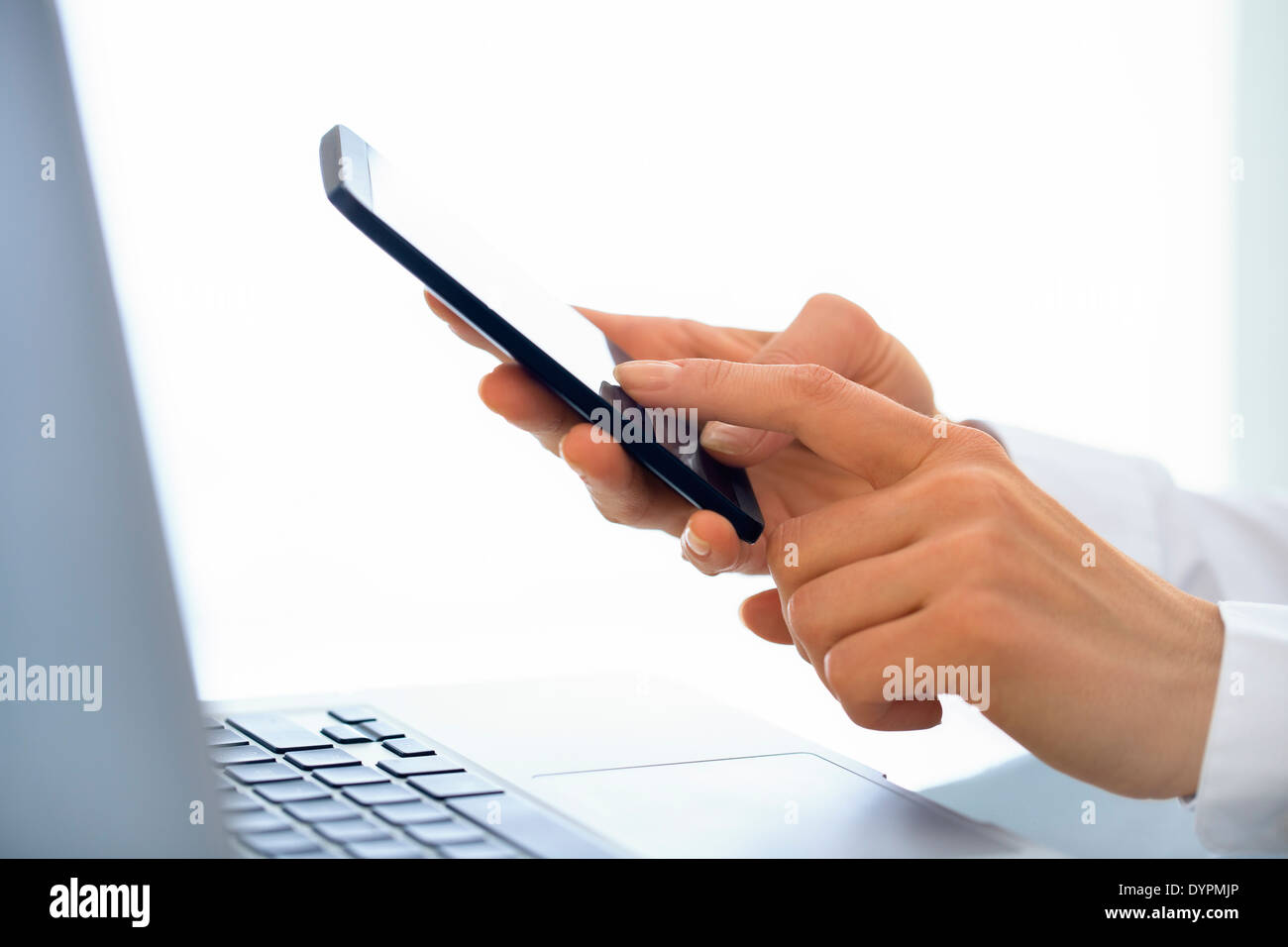 Businesswoman typing message on mobile phone in office. Stock Photo