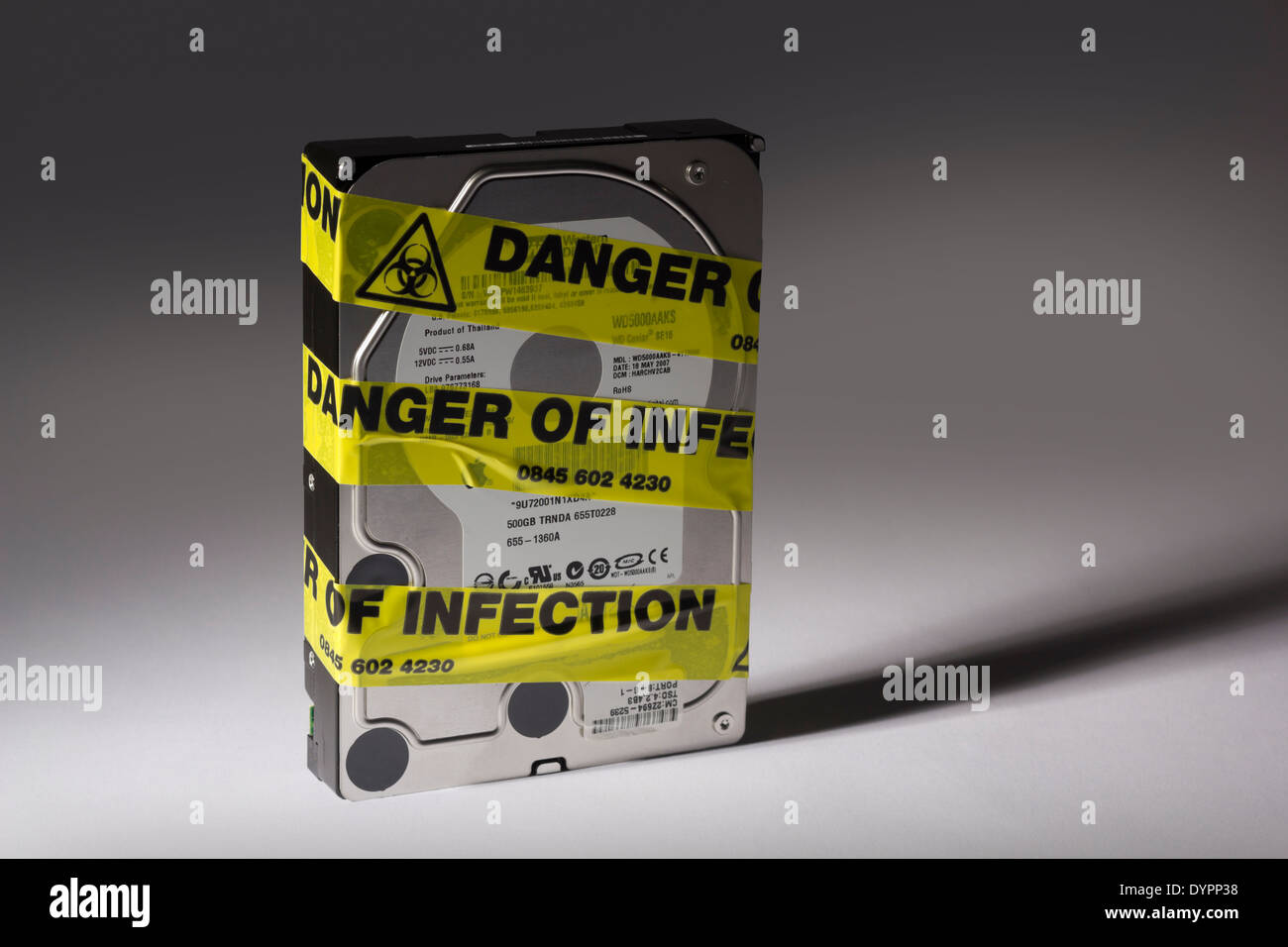 Computer Hard Drive With Yellow 'Risk Of Infection' Tape Around It. - Stock Image