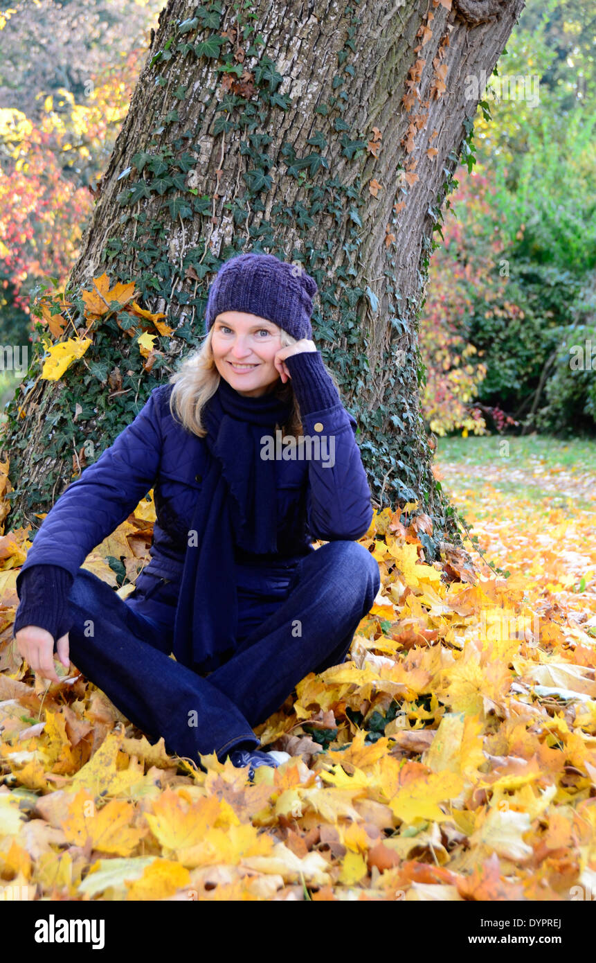 middle-aged woman sitting on autumn leaves  and looking at camera Stock Photo