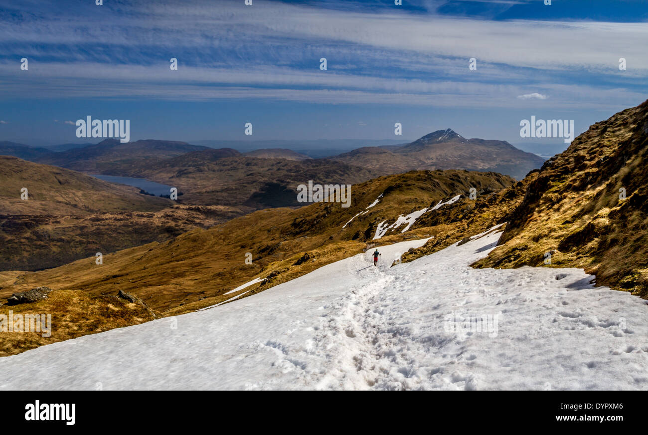 Walker descending snow on Ben Vane with views overlooking Loch Lomond and Ben Lomond, Scottish Highlands, UK Stock Photo