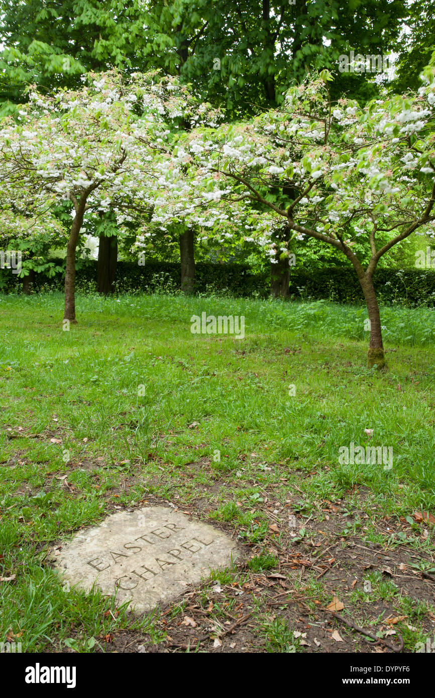 A stone plaque marks the entrance to the Easter Chapel with flowering cherry trees in background at Whipsnade Tree Cathedral, Bedfordshire, England - Stock Image