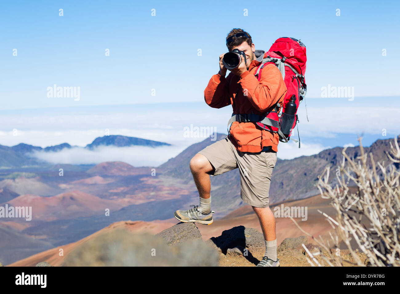 Photographer taking pictures outdoors on hiking trip. Outdoor nature photography. - Stock Image