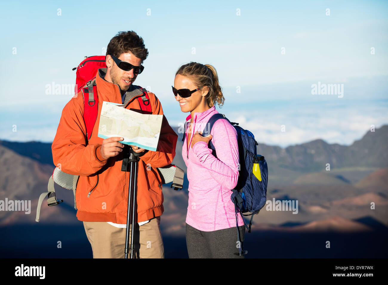 Hikers looking at trail map. Hiking in the mountains. - Stock Image
