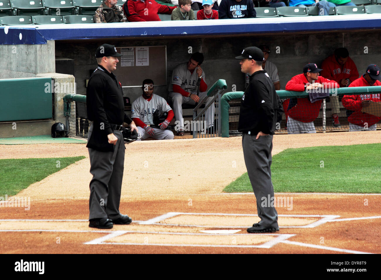 Two baseball umpires confer on the field. - Stock Image