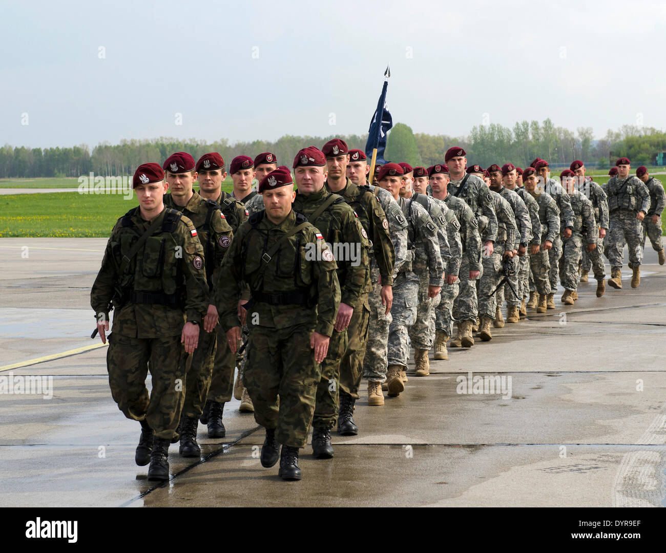 US Army paratroopers with the 173rd Airborne Brigade Combat Team arrive march alongside the Polish Army 6th Airborne Brigade on arrival April 23, 2014 in Swidwin, Poland. The soldiers were deployed to Poland and the Baltic nations as tensions with Russia rise over Ukraine. - Stock Image