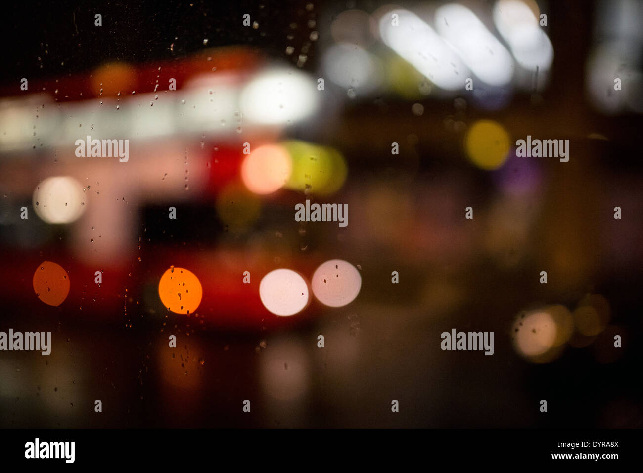 London rainy weather red bus window night lights - Stock Image