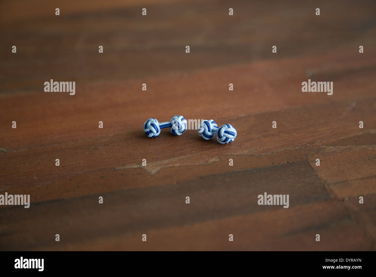 two-toned blue knotted cuff links on a wooden table - Stock Image