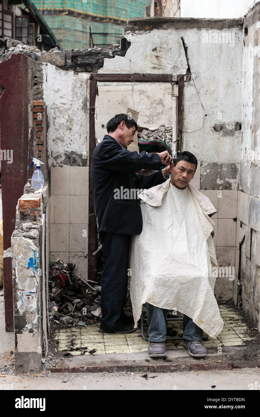 A barber cut the hair of a man at a demolished site - Stock Image