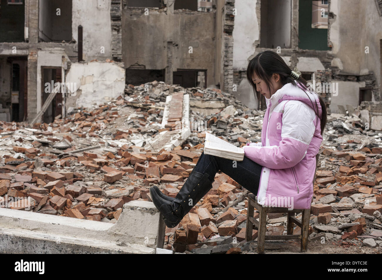 A girl reads a book at a demolished resident in Shanghai - Stock Image