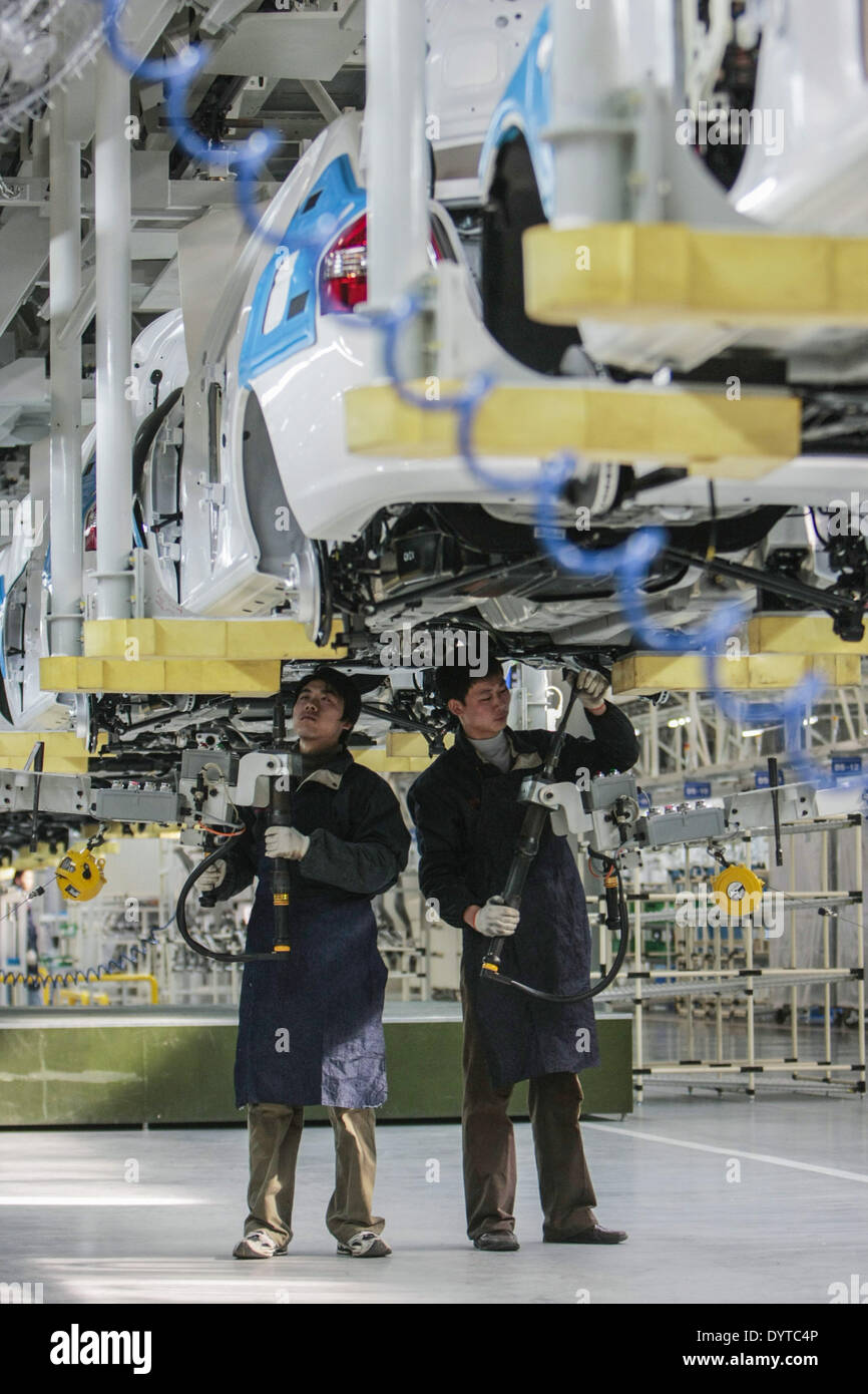 Workers work at a production line of KIA Motor's Cerato at YanCheng - Stock Image