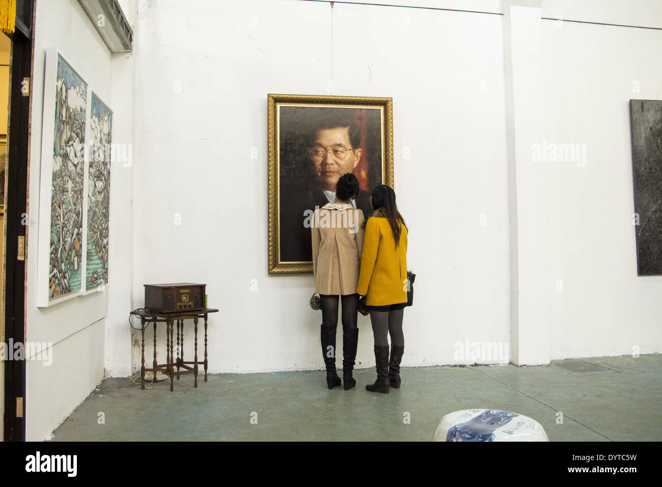 Two spectators look closely a painting of ex-President Hu Jintao in a gallery in Shanghai - Stock Image